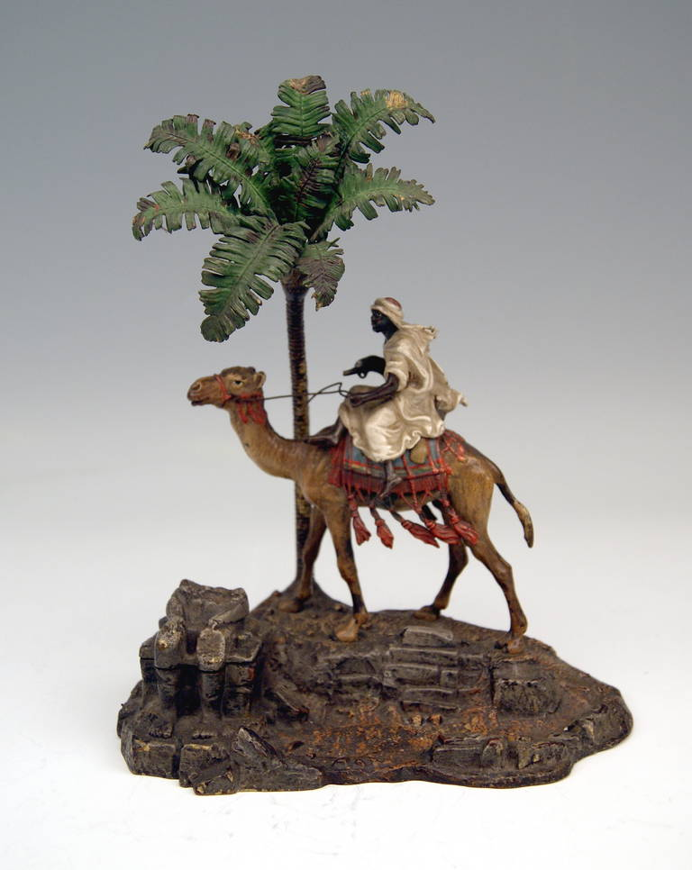 There is an Arab man  (warrior)  presented:  He rides on camel  /  beside him there is a tall palm tree visible.  -  The figurine group  is of  STUNNING LIVELINESS   (the details are amazingly sculptured)   !  