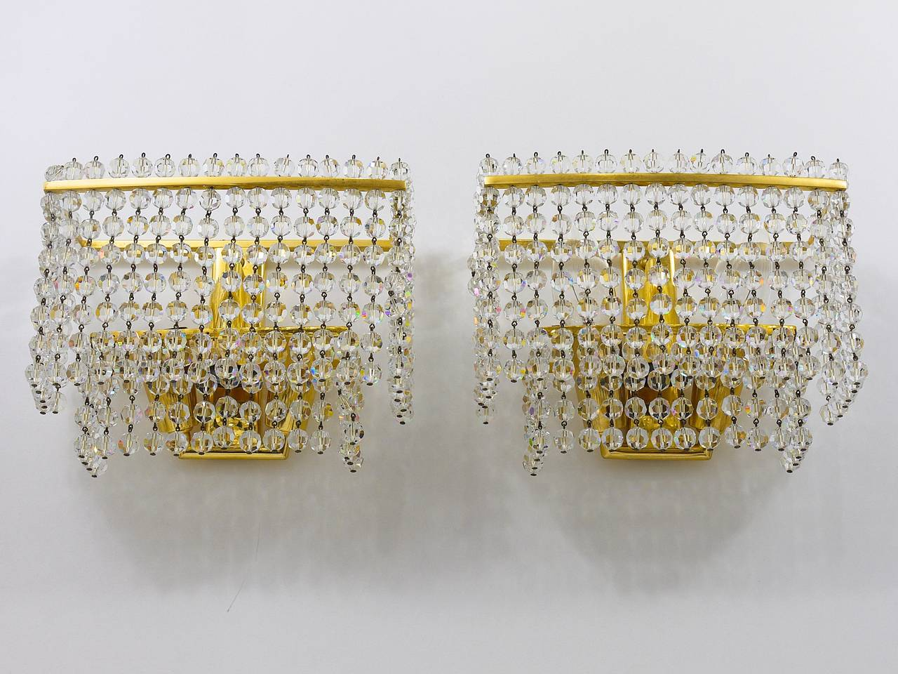A pair of gold-plated Mid-Century brass sconces. Designed and executed in the 1970s by J. L. Jobmeyr. Very beautiful lights, two layers of linked, highest quality leaded, faceted crystal pearls hanging on a gilded brass frame. Each sconce has three