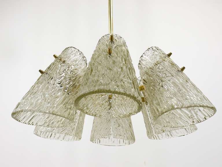 A beautiful brass chandelier by Kalmar Austria from the 1950s. Has lovely cone-shaped, textured glass lampshades. In good condition with patina on the brass.   Height without rod: 9 in Diameter: 21 in Total height: 32 in