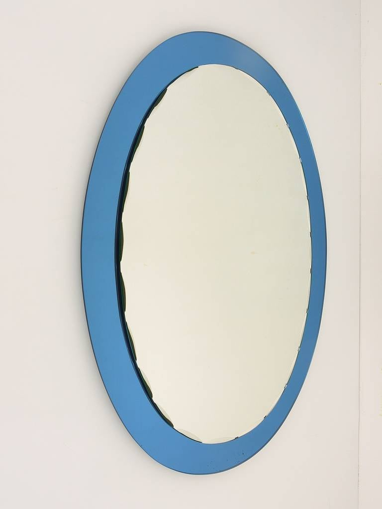 A very beautiful Italian wall mirror from the 1960s, made in Italy by Crystal Arte. Oval, scalloped faceted mirror with blue mirror backplate glass. Excellent condition, a few spots on the blue glass, but no damages.