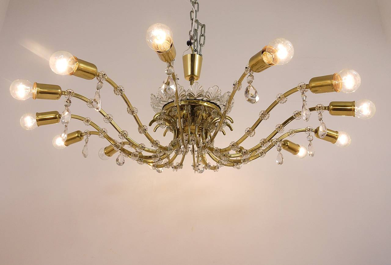 A very beautiful and huge brass and crystal glass chandelier, executed by Lobmeyr Vienna in the 1950s. Has 14 arms and very nice floral glass details. In very good condition with nice patina on the brass. Measures: Diameter 44 in, the total height