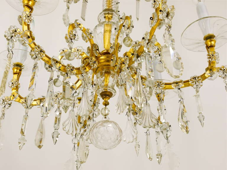 A very elegant baroque crystal cut-glass gilt chandelier. Executed in the 1940s-1950s by the Lobmeyr Vienna. Luxuriously fitted with a lot of different faceted high-quality crystal glass stones. Six arms, the base is made of gold-plated iron. A very