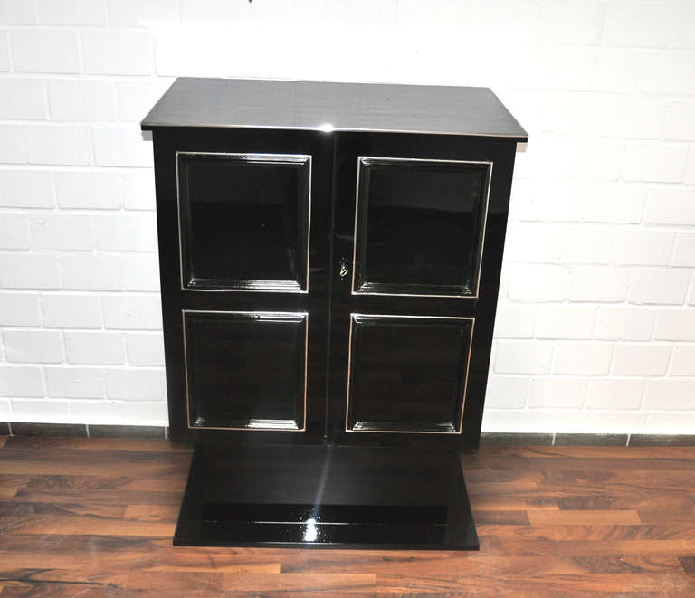 Petite Art Deco Cabinet/Bar with a square body and shelves for storage. Refinished with black piano lacquer and polished by hand.   - beautiful straight body - discreet chrome trims - hand polished - 2 large doors  Any questions? Please don't