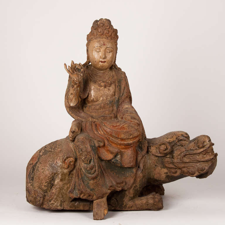 Wooden buddha sitting on a lion or dragon, 18th century or earlier, China.
