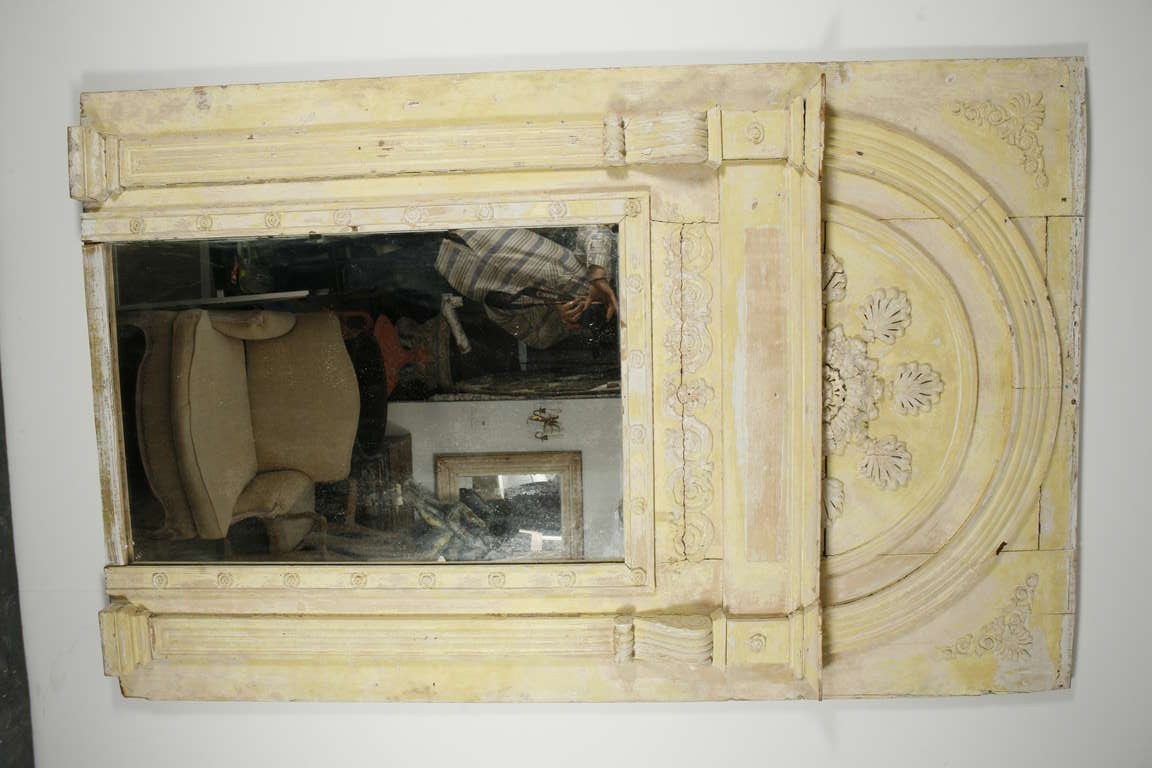 a large yellow painted plaster and wood trumeau mirror