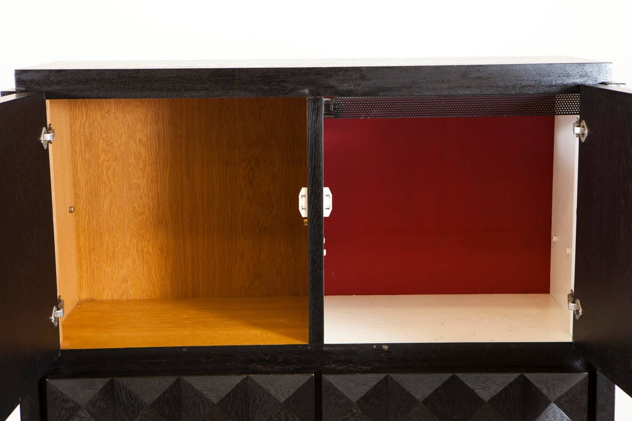 An ebonized Belgium Brutalist style bar cabinet with graphic front door with detail of checkered pattern. Four doors with one cube painted white/red accent with others in natural oak finish. Interior wiring set for European standards.