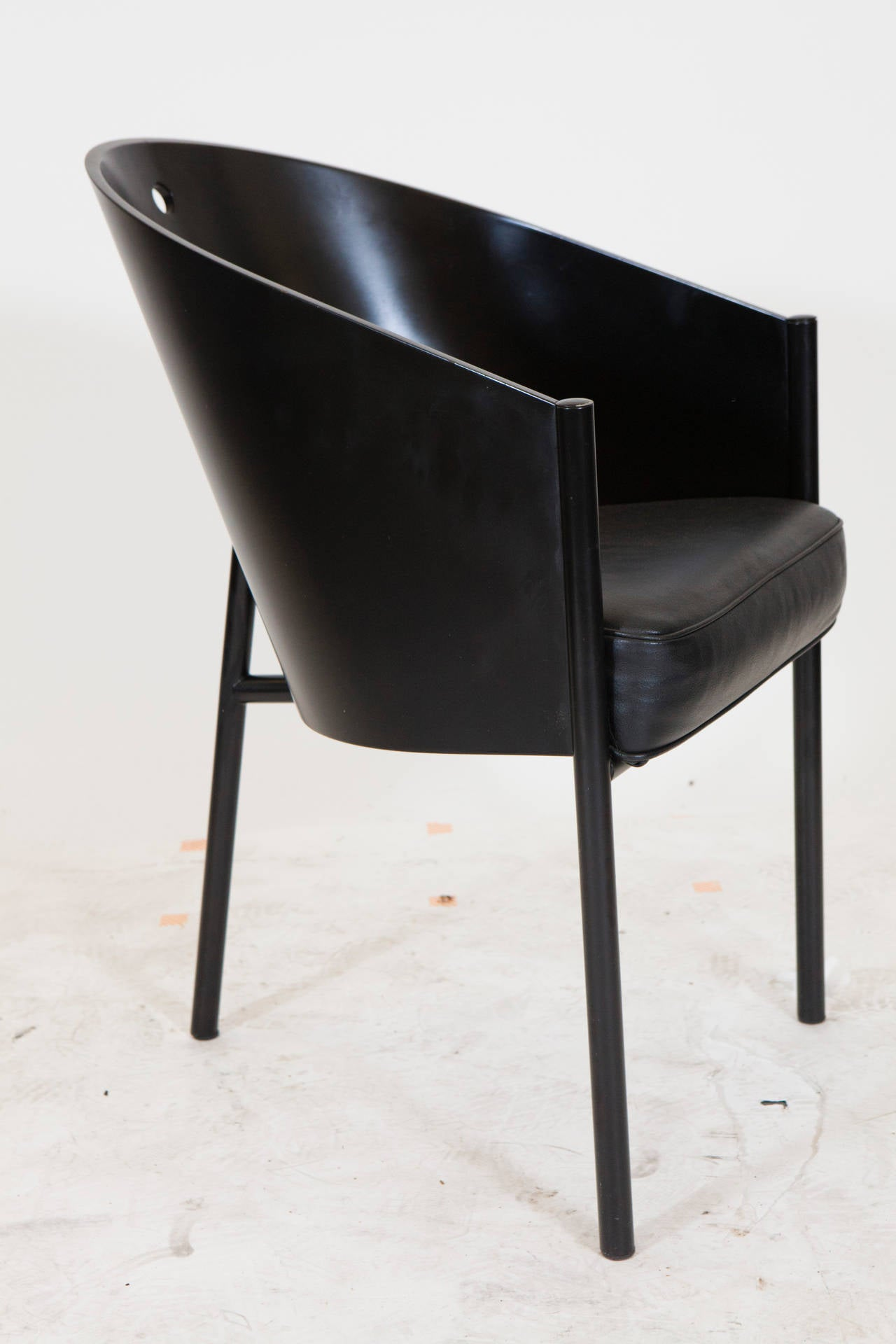 A set of eight three-legged black chairs. Designed by Philippe Starck in 1982 for the Cafe Costes in Paris these chairs were produced by Driade/Aleph an Italian company in the late 1980s. Chairs have a black metal tubular frame with black laminated