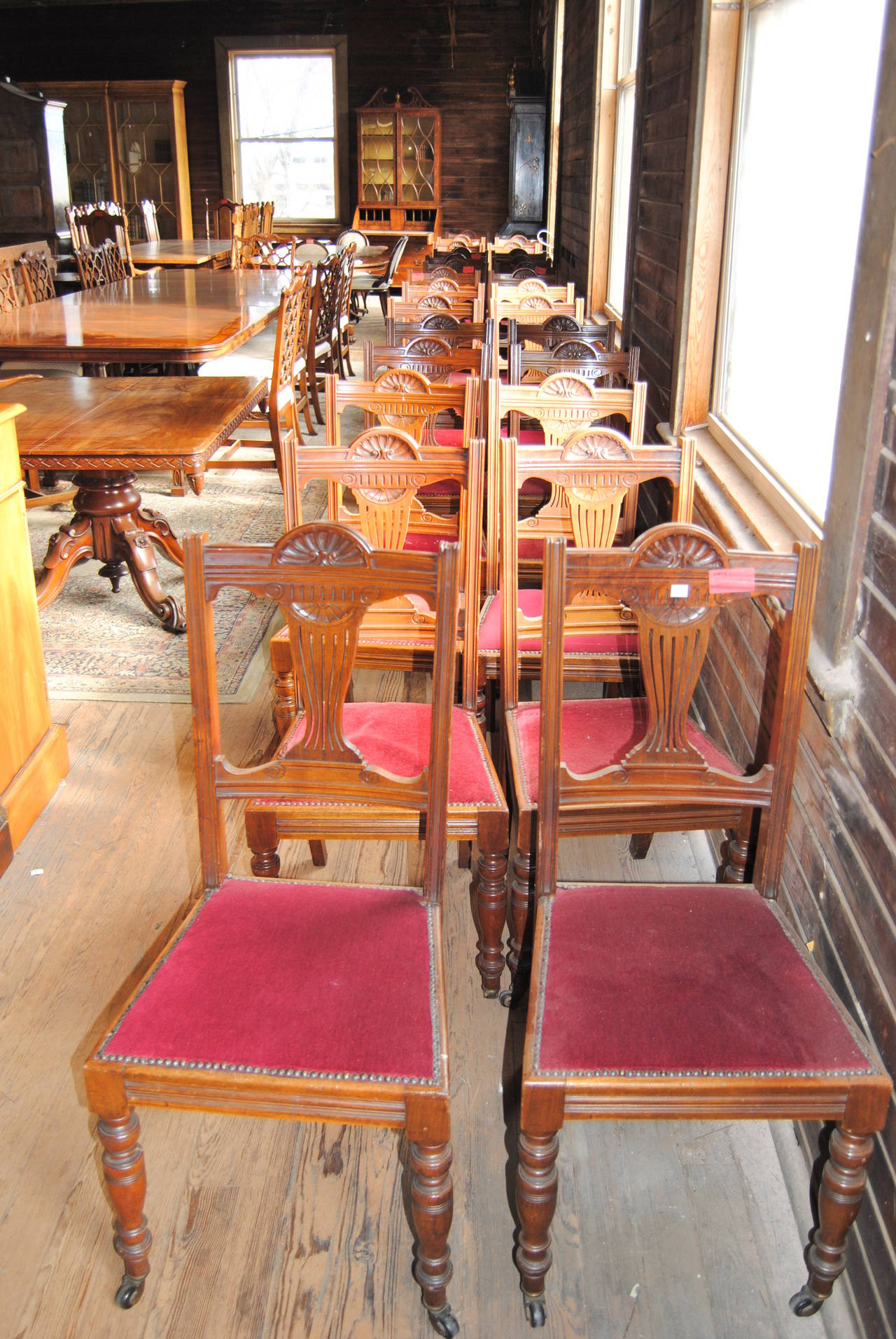 This is a matched set of 18 solid walnut side chairs made in England, circa 1870. The chairs have nicely reeded uprights on the back right and left. The splat in the chair back nicely shaped and is pierced and carved. The seat frame on the front,