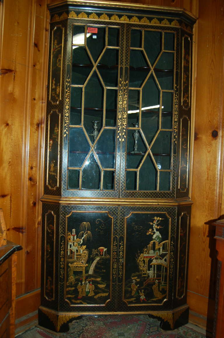 English corner cabinet, made circa 1780, in lacquered gilt chinoisoire. Stunningly beautiful lacquered gilt chinoisoire on a black ground. Bracket feet to the base. 13 pane astrical glazed glass in the upper doors. Nice old wavy glass. Three