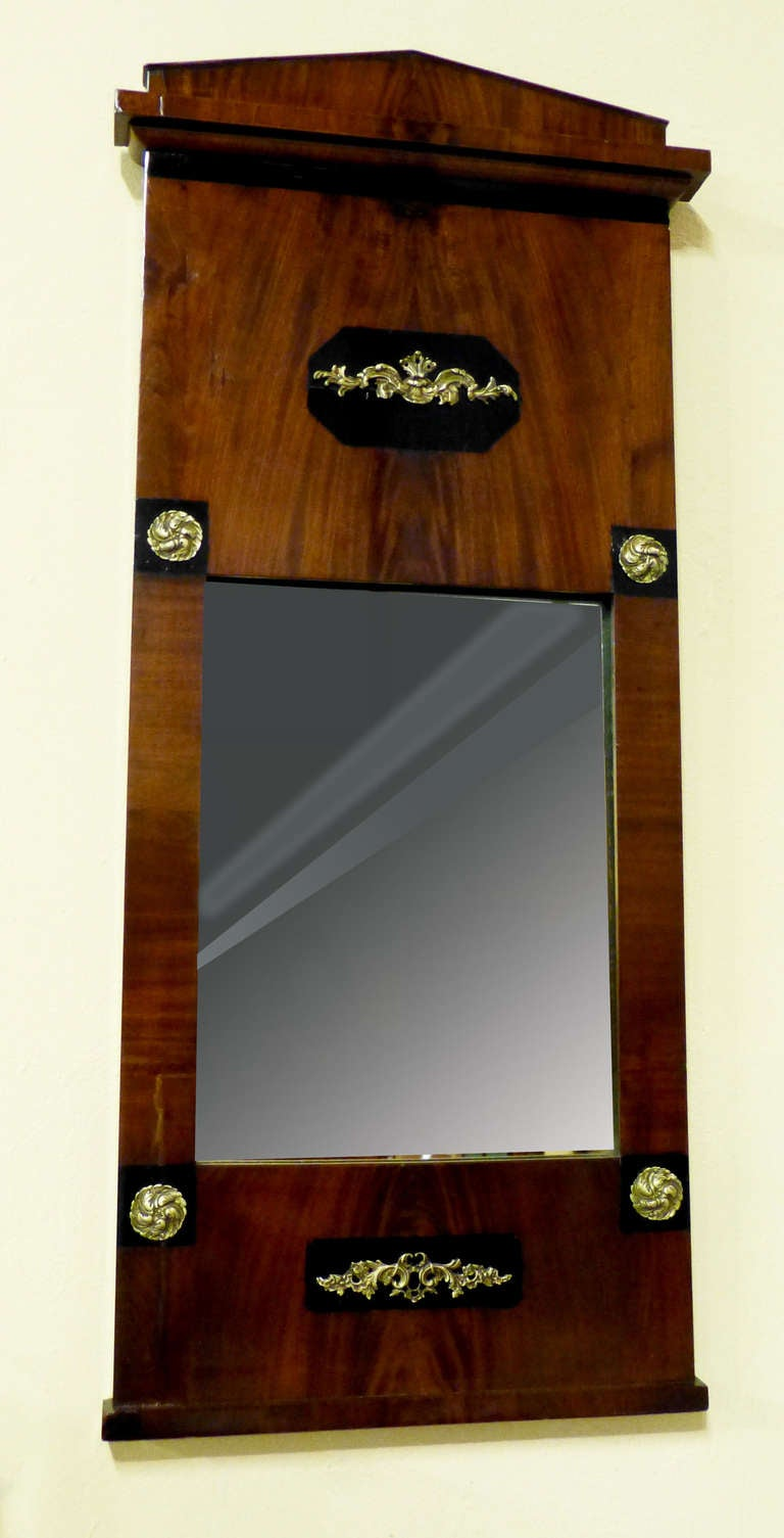 Figured mahogany late Empire early 19th century  Biedermeier mirror bearing Empire gilt brass decorations over ebonised backrounds. The pediment is of the Schinkel type similar to  Greek Doric, over flat mouldings and base. The mahogany is finely