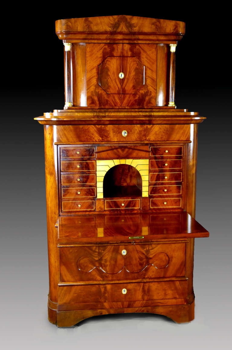 Outstanding figured mahogany Biedermeier tall secretaire with columned tabernacle and rounded Doric Schinkel type pediment. The fall front door also with figured mahogany writing surface and hidden weights; when open, it reveals an attractive