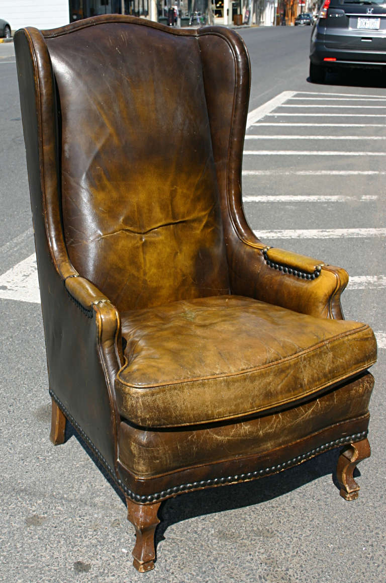 A nicely distressed and with good patina leather wing chair. Leather in a burnt caramel & High Leather Wingback Chair at 1stdibs