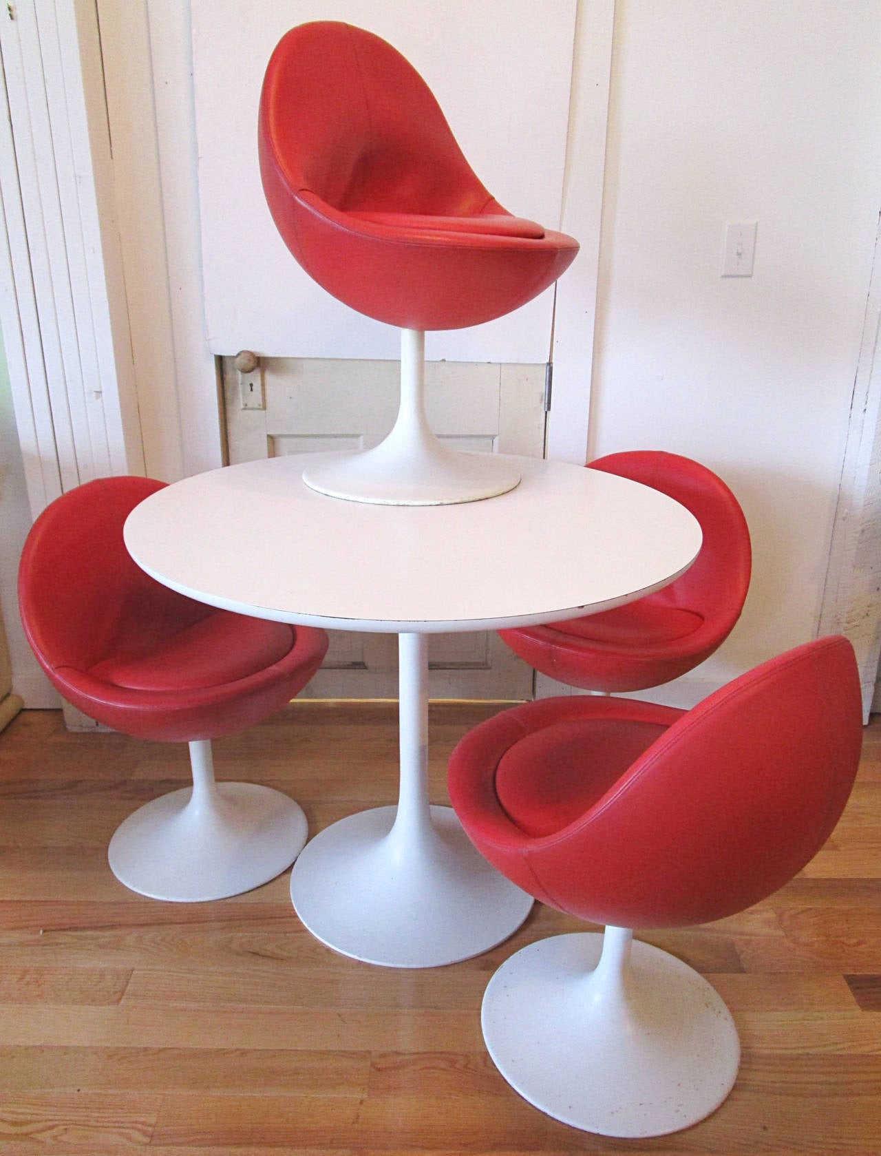 """Reminiscent of the Saarinen tulip set, this Borge Johanson set came out in 1968. Set includes four red egg pod swivel chairs and a 35.75"""" round by 29""""h white laminate top all on white enameled tulip bases. Chairs 21"""" D x 30"""" H, 17"""" Sh."""