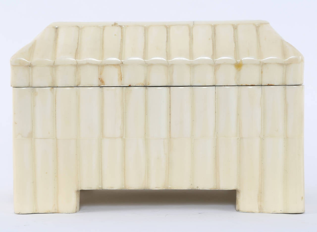 Rectangular, four-leg box clad in lacquered, convex bone tiles. Hinged top with felt-lined interior. Remnants of a paper label.