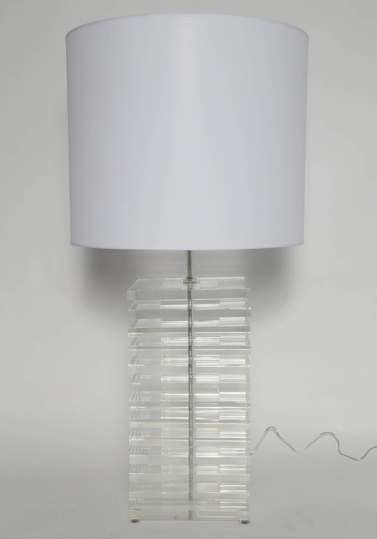 Enormous and extremely heavy statement lamp consists of stacked alternating large and small 1-inch-thick Lucite squares, circa 1970s. Rewired with new three-way socket. Lucite base is 12