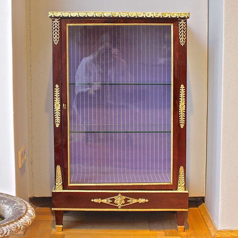 A Mahogany ormolu-mounted Louis XVI style display cabinet mounted with finely chased ormolu casts showing on the top ribbon tight swags of drapery, on the side flower heads with stylized foliage, on the bottom a lozenge framed mask, lotus leave cast