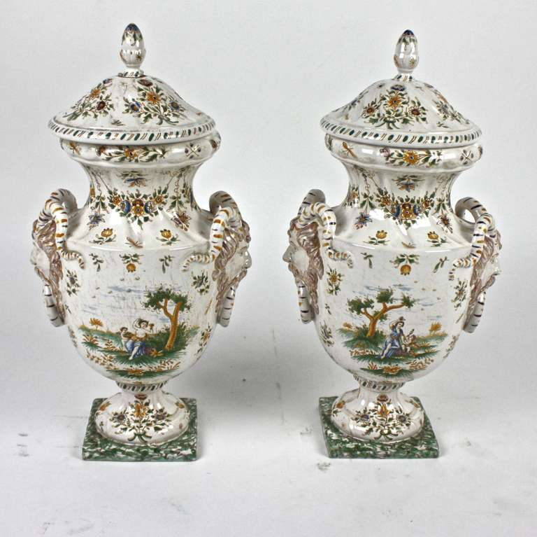A Pair of faience vases richly decorated with classical mythological scenes (Cupid and Psyche), flowers, foliage and two grotesque mask handles. The grotesque animal decoration found on pieces made at the Moustiers faïence manufactory of