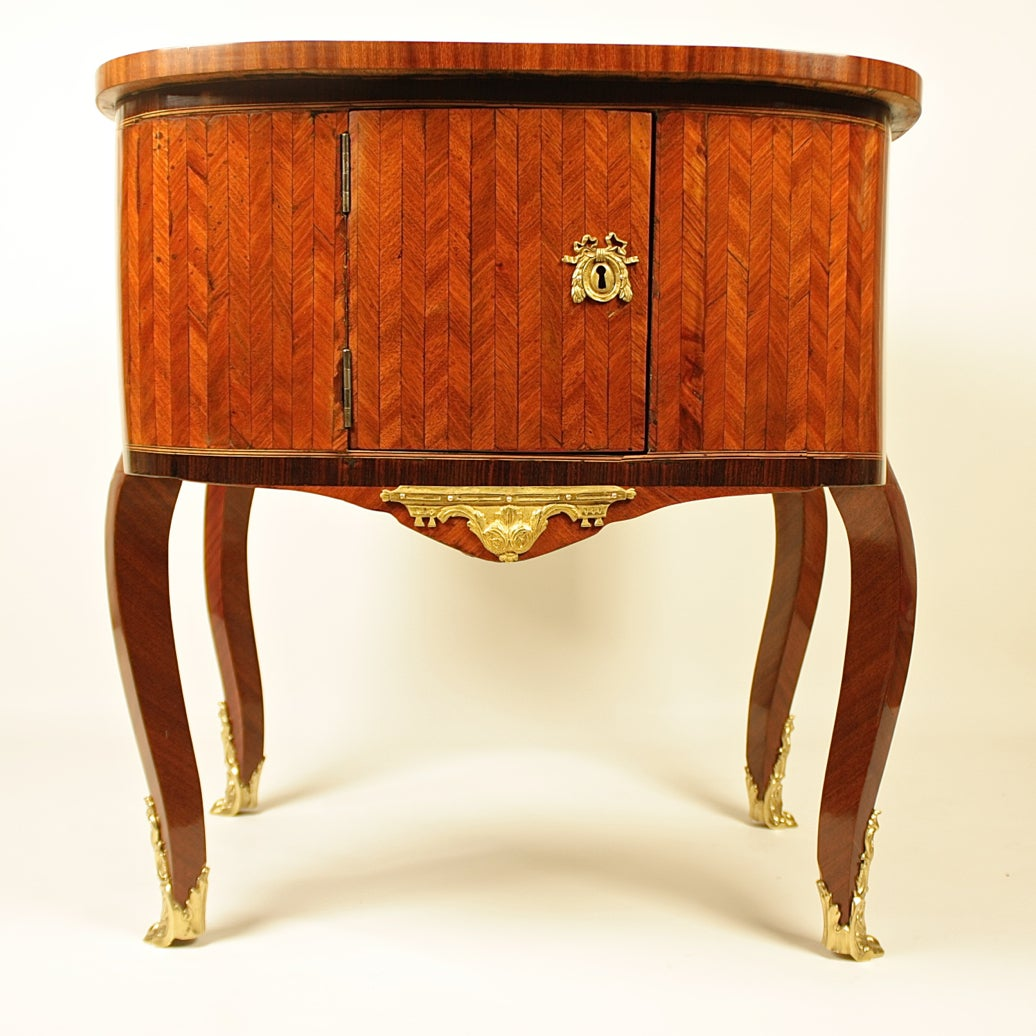 An 18th century gilt-bronze mounted double-face Bonheur du jour panelled with herring-bone parquetry. The kidney shaped top with one frieze drawer and an opposing dummy drawer flanked by two cupboard doors enclosing a shelf, with scrolled acanthus