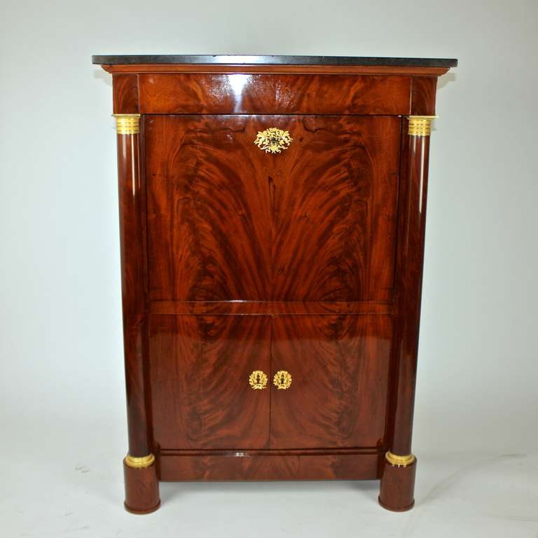 A French Empire mahogany and ormolu mounted writing cabinet surmounted by a Belgian marble-top, fitted with a frieze drawer, the fall inclosing a fitted interior with tooled original leather lined panel, a compartment with seven various small