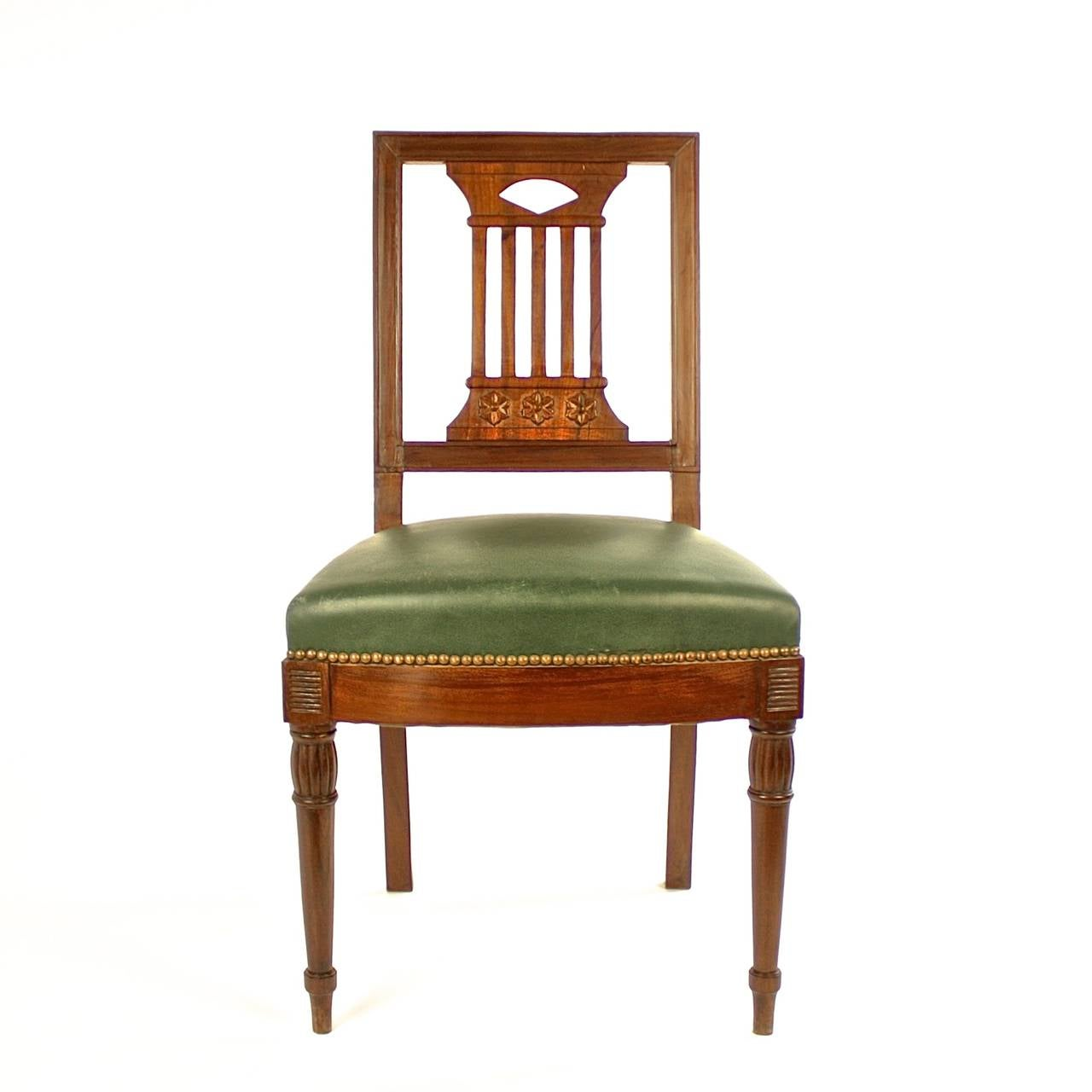 Pair of early 19th century mahogany side chairs in the manner of Bellange frere. Raised on turned tapering front legs and sabre rear legs, carved with pierced splades in the shape of a pilaster and adorned with carved paterae, upholstered with dark