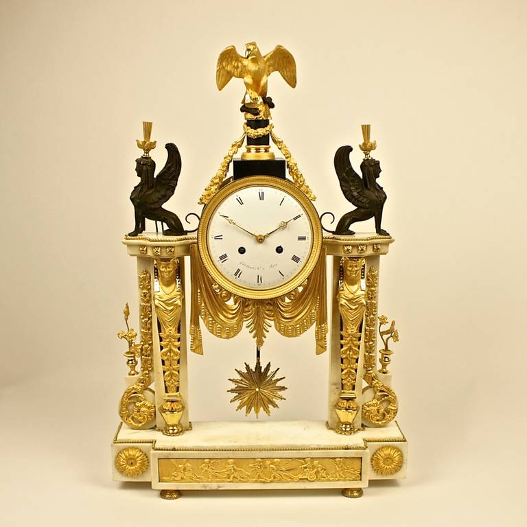 Exceptional late 18th century ormolu mounted mantel clock, marble with extensive Egyptianate ormolu mounts with scrolls and festoons, eagle finial flanked by two black patinated bronze female sphinx, base with relief plaque of frolicking putti,