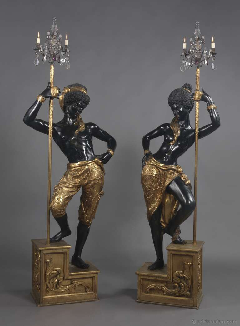 A fine pair of ebonised and Gilt Blackamoor figures supporting three-light candelabra.  The figures are finely carved as male and female blackamoors, each standing in a contra posto pose with one leg raised on a gilt carved step. In their right