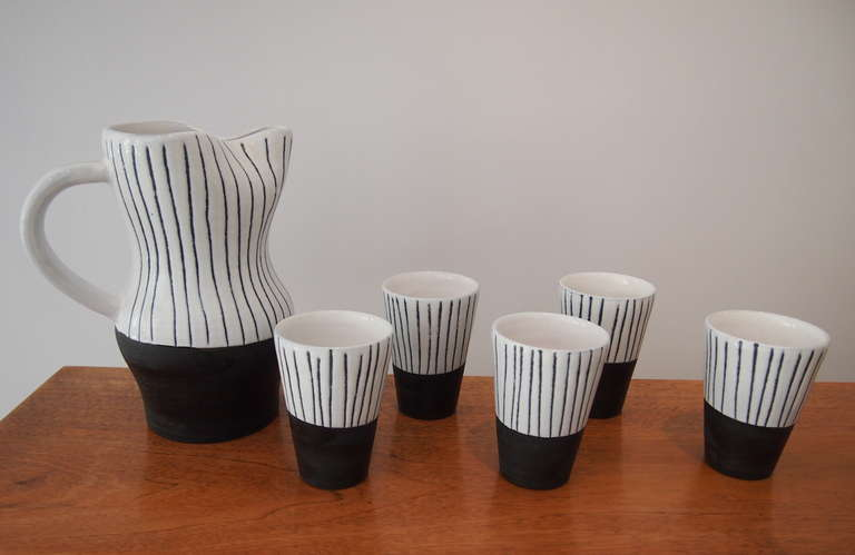 Jacques Innocenti (1926-1958). Drinking set composed of a jug and five glasses in black and white enameled ceramic. The jug is signed