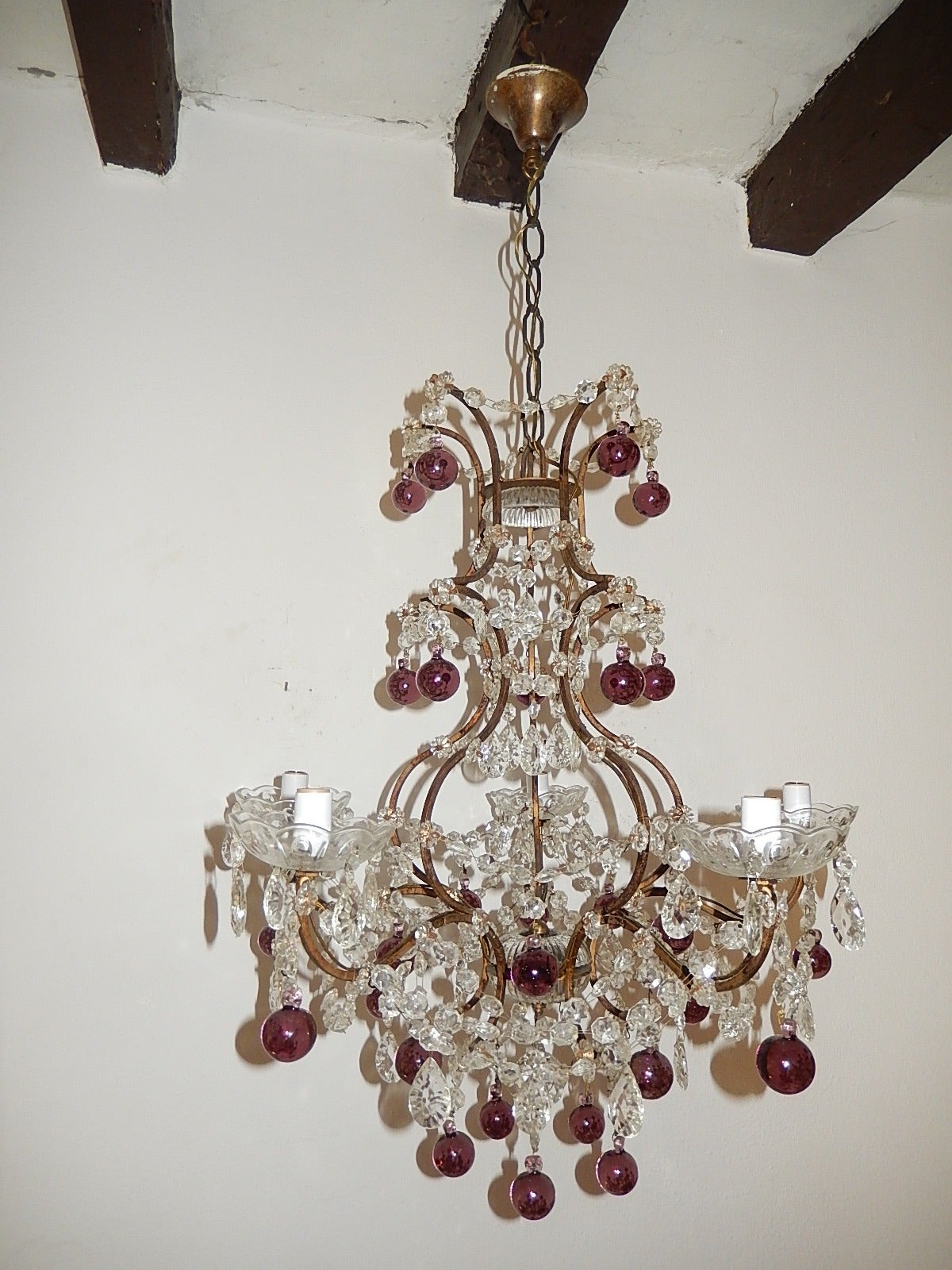 Housing 5 lights, sitting in crystal bobeches dripping with rare cut prisms.  Tiers of crystal swags and 30 rare short bulbous Murano balls in amethyst.  Adding another 12 inches of original chain and canopy.  Free priority shipping from Italy.