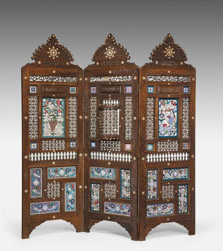 A rare 19th century Middle Eastern three-fold screen with elaborate bead work, rosewood, pearl inlay and finely enamelled panels of figures, birds and foliage, the panels with Kufic inscriptions.