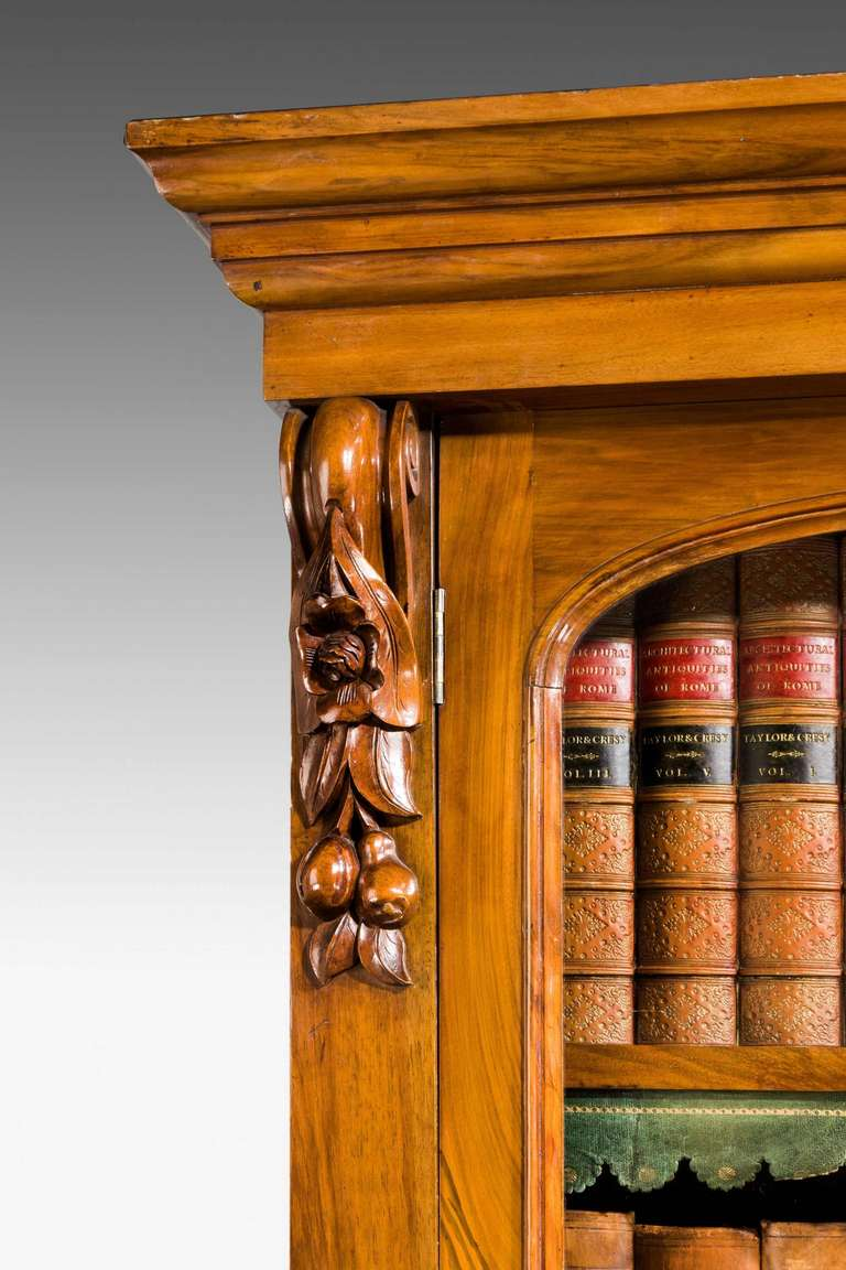 Good walnut and burr walnut bookcase with carved capitals and the fielded panels to the lower doors with matched timbers.