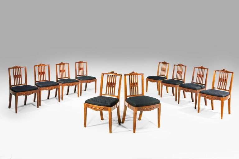 Set of ten mahogany framed dining chairs with square section backs, the top rails with applied ribbons, the bow front seats with drapery swags, six circa 1800 and four circa 1900.