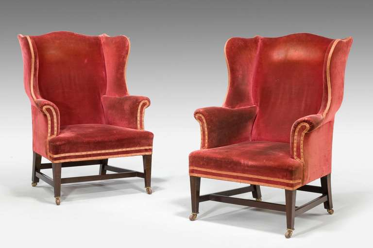 An attractive pair of shapely mahogany wing chairs of Chippendale design with square supports and cross stretchers.