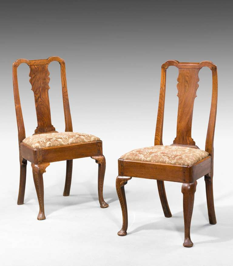 Set of four George I period elm cabriole leg chairs of pegged construction.