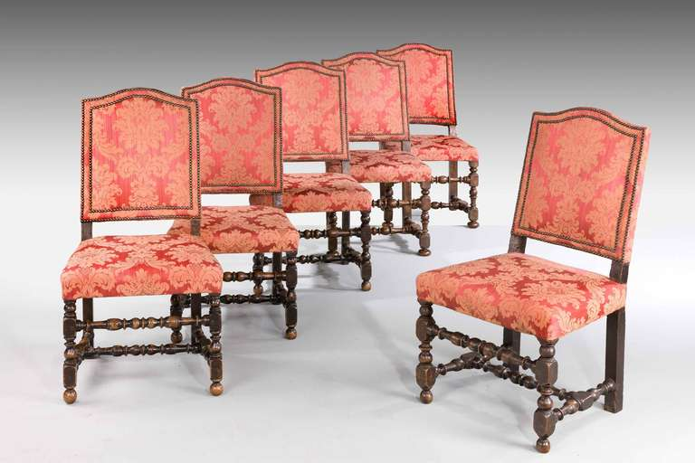 Set of six 17th century style walnut chairs with finely turned supports and cross stretchers, the backs double studded.