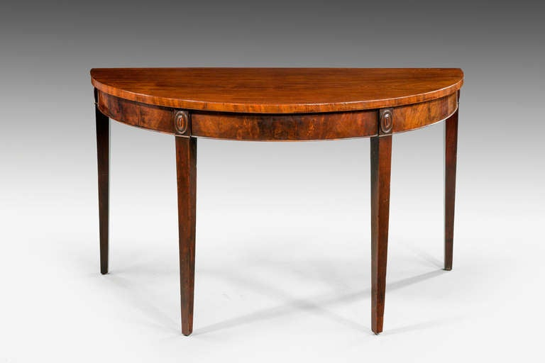 A good George III mahogany demilune serving table, the particularly fine timbers are well patinated, crossbanded edge over finely figured veneers.