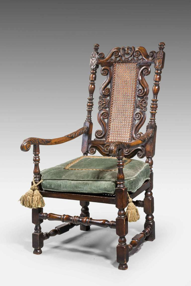 An attractive 17th century style walnut armchair with cane seat and back panels and excellent carved detail.