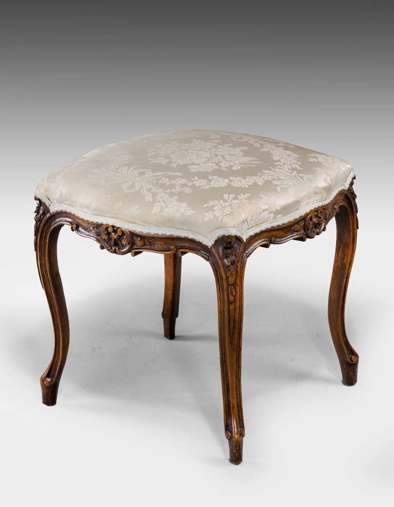A beech framed Stool on cabriole supports and delicate decorative carving.