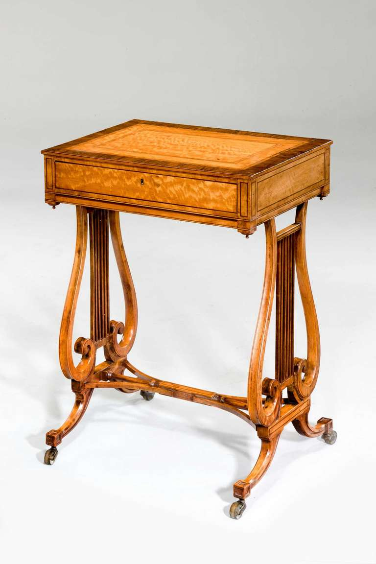 An exceptionally good late 18th century satinwood work table with finely figured rosewood crossbanding, delicate lyre shaped end supports with unusual central veneered uprights, scroll terminii over swept feet.