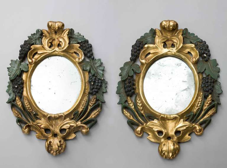 An attractive pair of oval Italian mirrors, the gilded and polychrome decoration now oxidised, elaborate wheat ears and grapes to the outer frame.