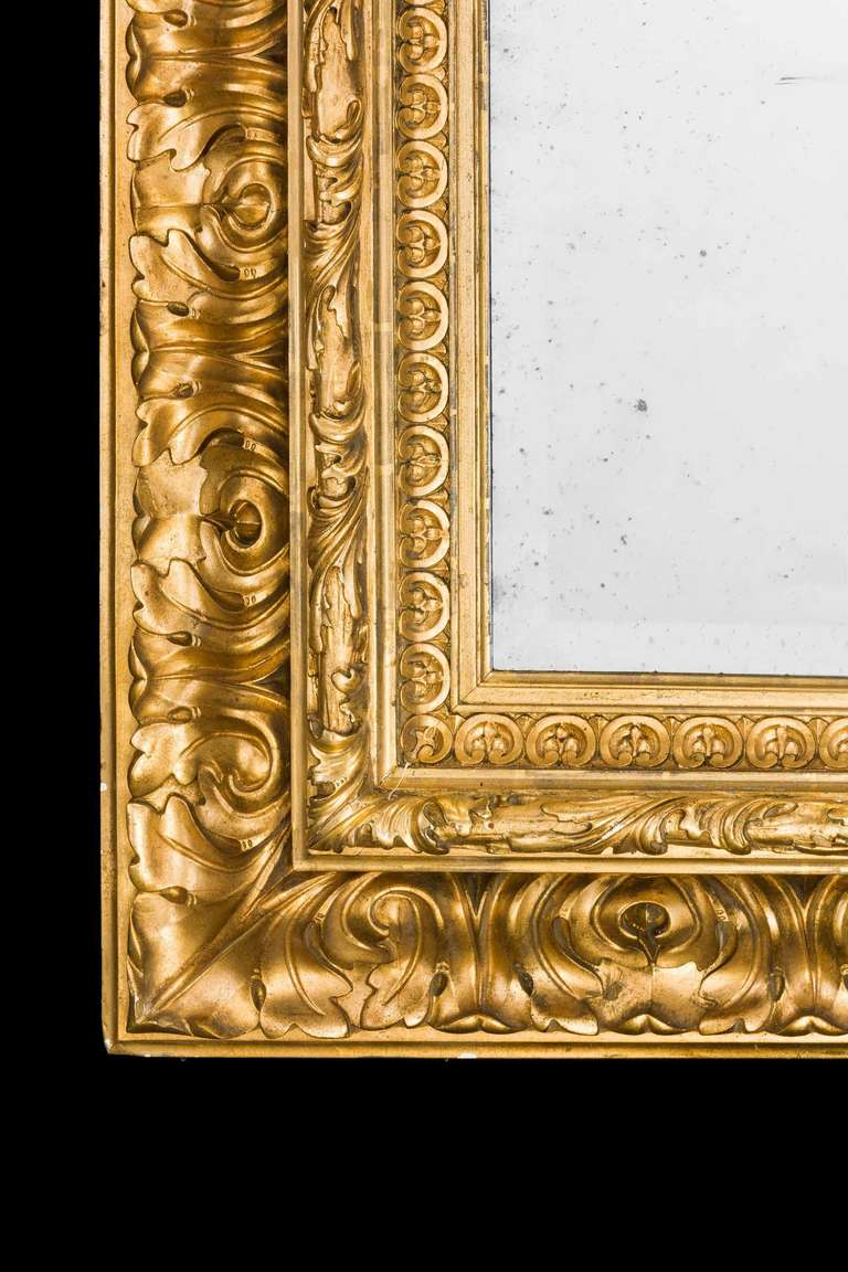 Fine Italian 19th century giltwood mirror with an antique bevelled plate with scroll carving at three levels, gilding in overall good condition.