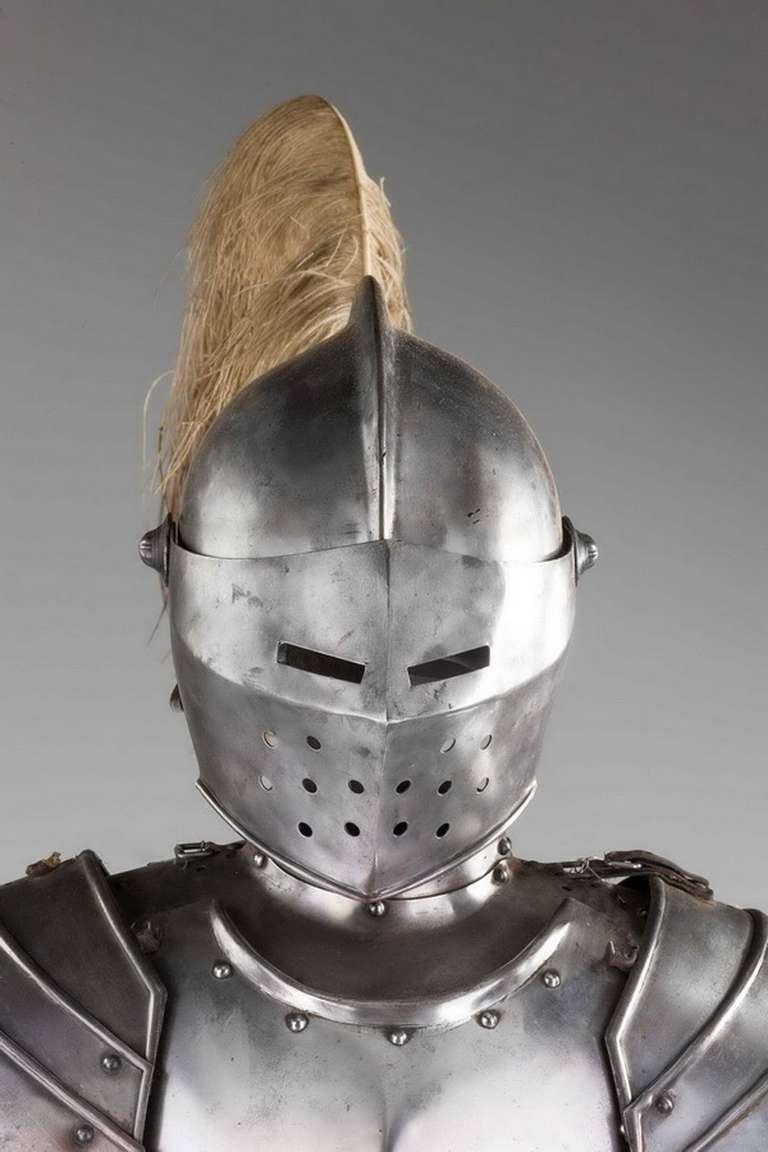 Mid-20th century close helmet suit of armour, comprising visor, besagues, breast plate, couters, rerebraces, vambraces, gauntlets, tassetts, cuisses, poleyns and sabatons.