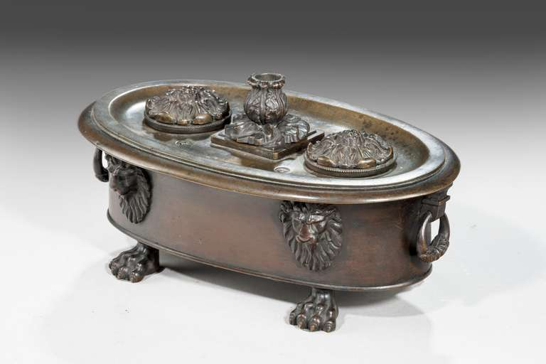 A good Regency period bronze oval Encrier, the lid with a candlestick, the two departments with stylised flowers, the main body well cast standing on paw feet. Original bronze patina. Very probably made by Messenger and Phipson.  Samuel S