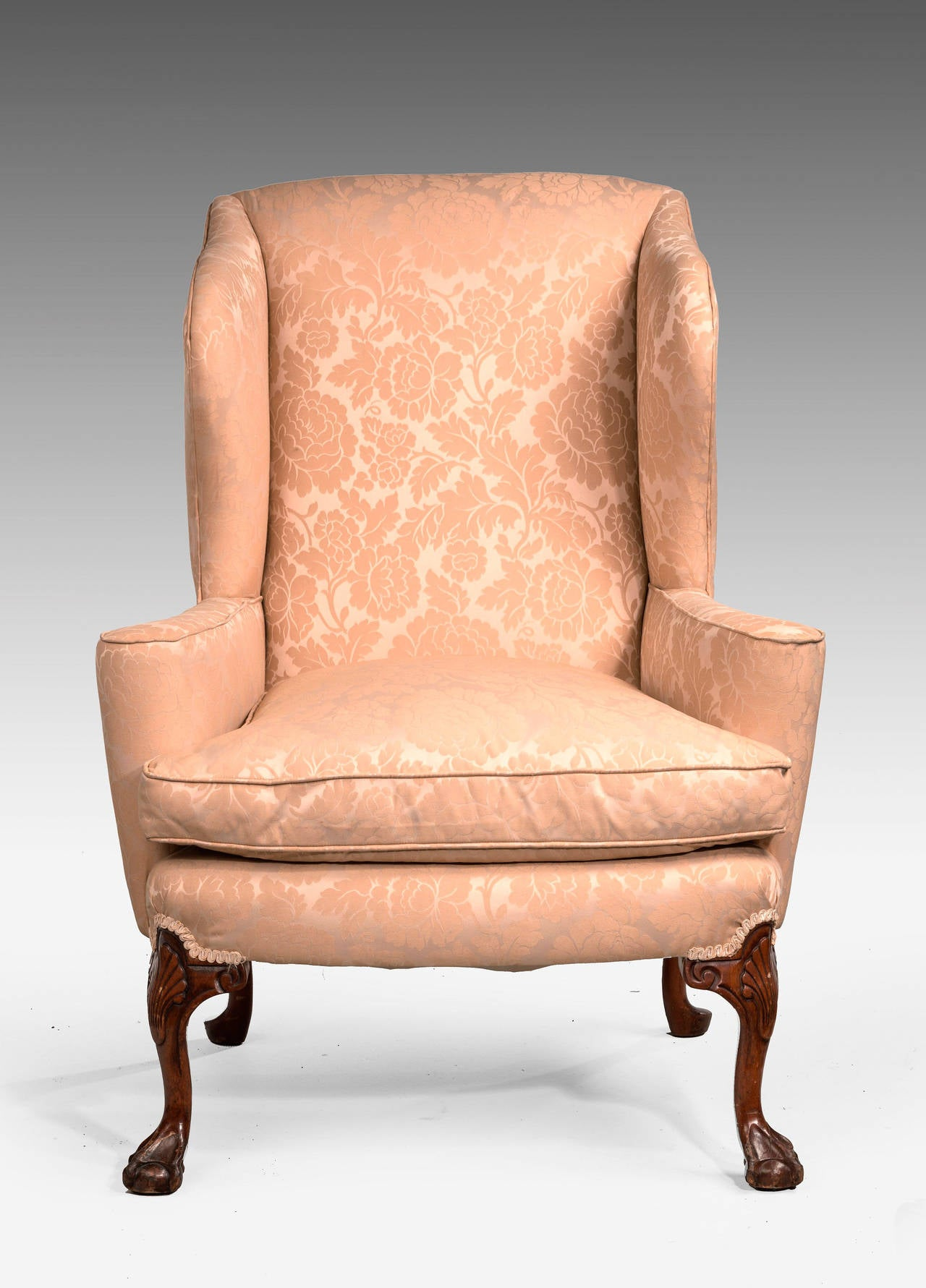 A walnut-framed wing chair of George II design. The cabriole front support with shell and leaf carving over claw ball feet. Late 20th century. Excellent quality upholstery but not newly covered.  An 18th or 19th century wing chair is an easy chair