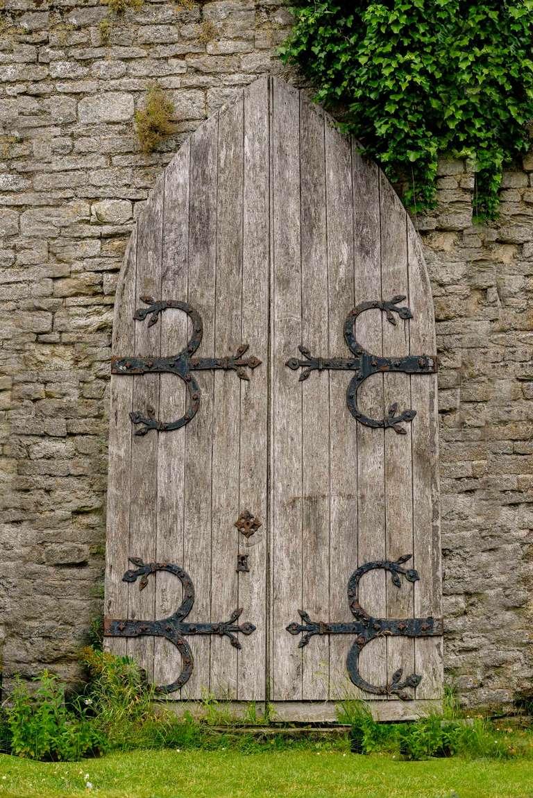 A pair of massive mid-19th century oak arched doors of Gothic design, retaining original iron strap-work.  RR.