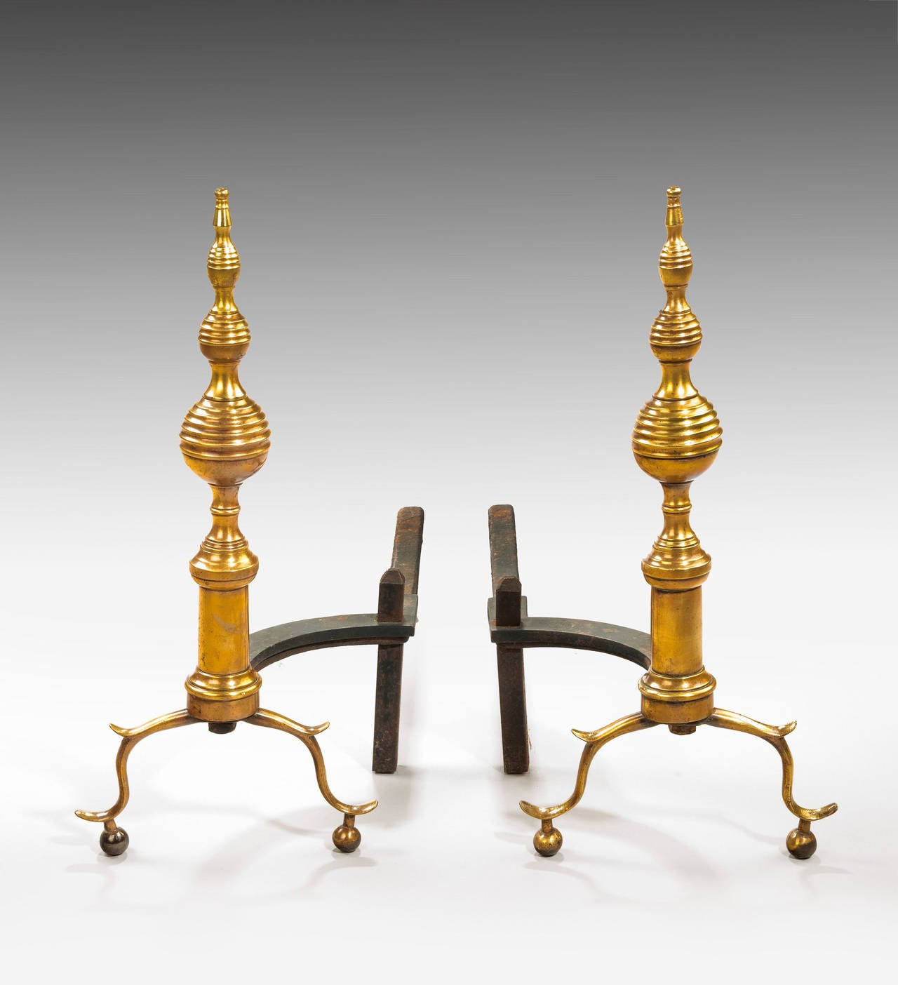A pair of brass and cast iron andirons, the central sections of bee hive form. On spread terminals.