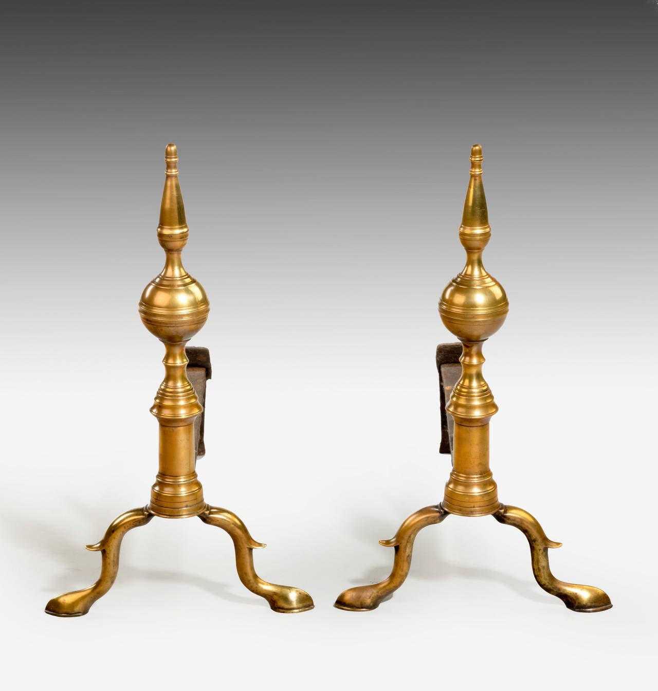 An attractive and well made pair of Andirons of conciliar form. Resting on pad feet.   An andiron is a horizontal iron bar upon which logs are laid for burning in an open fireplace. They are usually used in pairs to build up a firedog in American