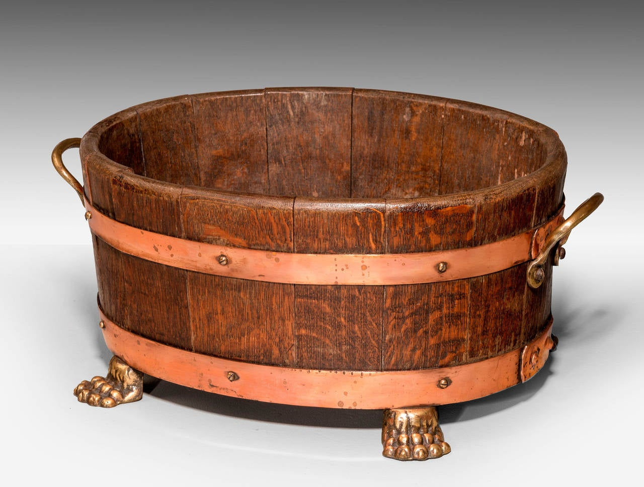 A copper bound coopered planter of oak. With lion support feet, and shaped handles.