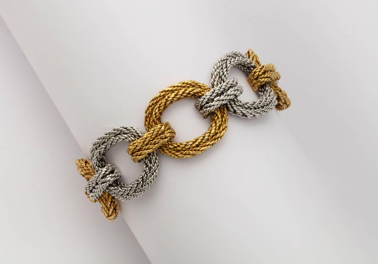 A handsome 1970s unisex bracelet by Cartier of 18K gold in colors of a platinum colored white gold and deep yellow gold, created by the finely braided rope-like texture. Gold and registry marks, Cartier and Italy. 3/4 inches wide x 7 1/2 inches long.