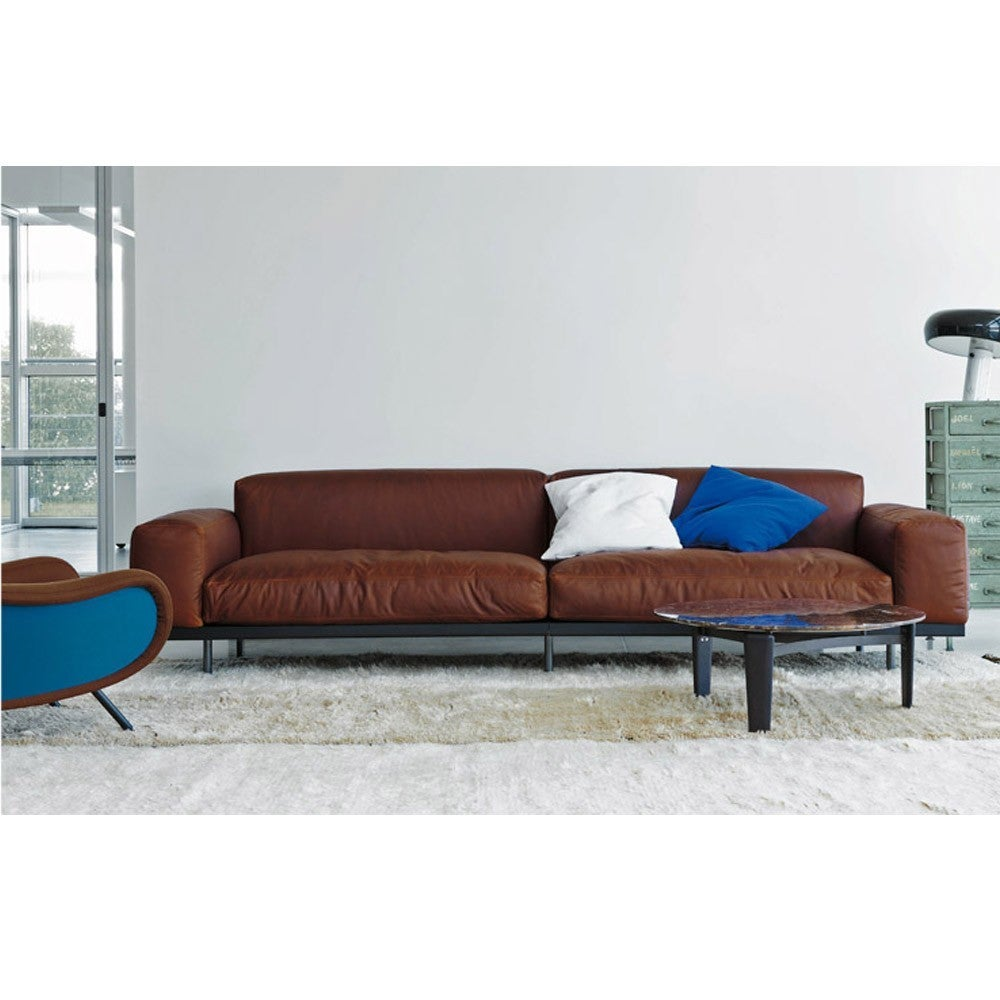 With the strict form of Umberto Asnago's Naviglio sofa, its overall appearance is pleasantly softened through lines created by the clever use of materials and upholstery. This sofa was created with great attention to detail and composition,