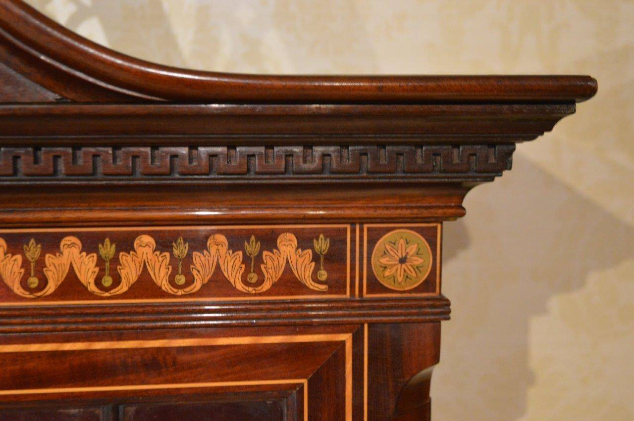 A stunning exhibition quality mahogany inlaid antique bookcase by Edwards & Roberts of London. The upper section with a pierced fretwork swan neck pediment with Greek key moulding and marquetry pen-work frieze. The twin astragal glazed doors open to